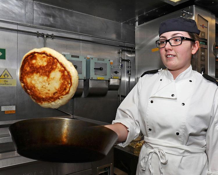 Chef Rebekah Atkinson cooking pancakes on HMS Albion