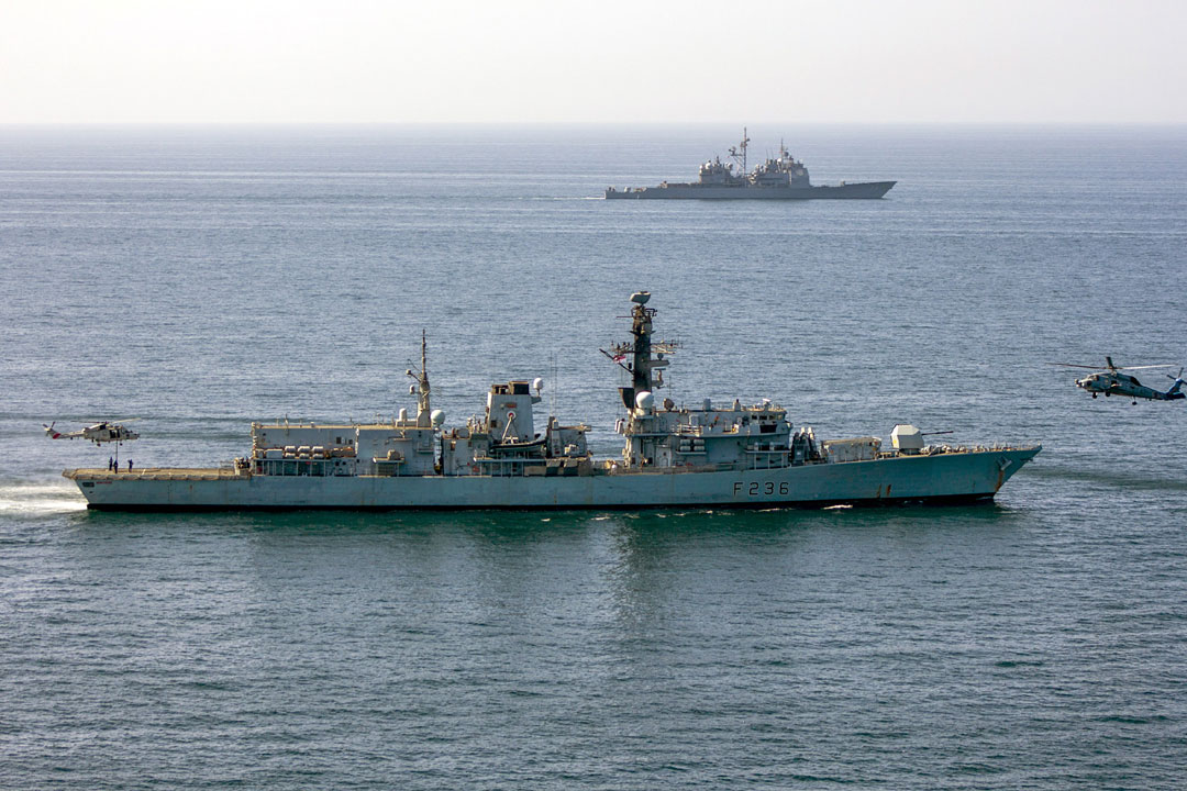 Omani and US Navy helicopters work with HMS Montrose with American cruiser USS Port Royal in the background
